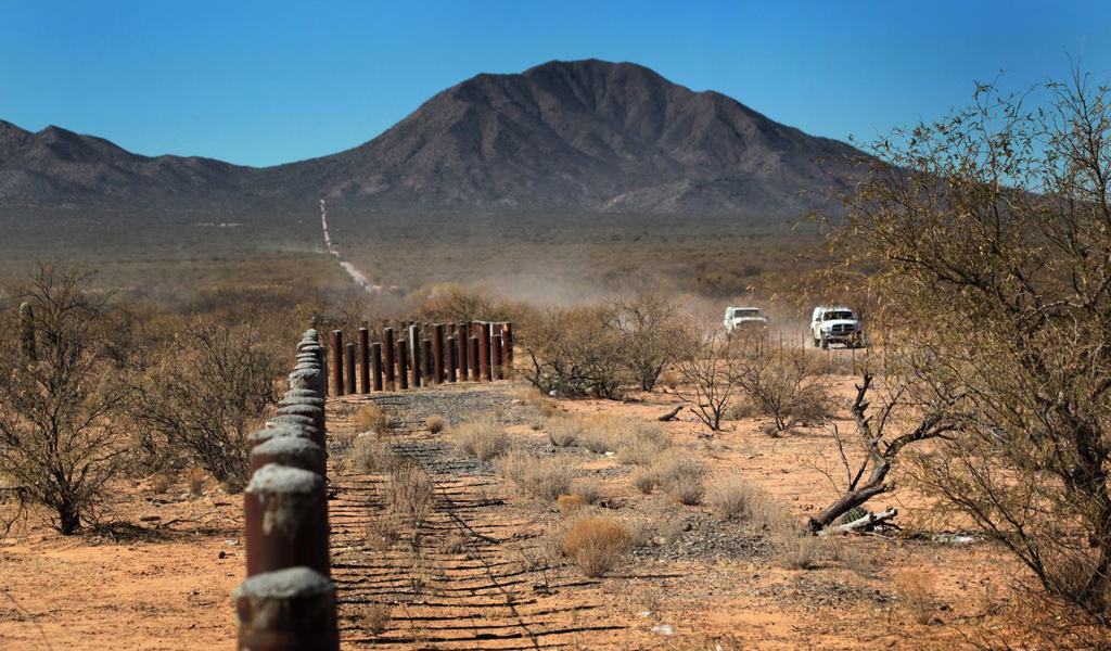 TOHONO O'ODHAM NATION, AZ - JANUARY 18:  U.S. Border Patrol agents drive along the porous U.S.-Mexico border fence which stretches through the Sonoran Desert on January 18, 2011 in the Tohono O'odham Nation, Arizona. The Native American reservation, which stradles 72 miles of the U.S.-Mexico border, is a key crossing point for narcotics entering the United States.  (Photo by John Moore/Getty Images)
